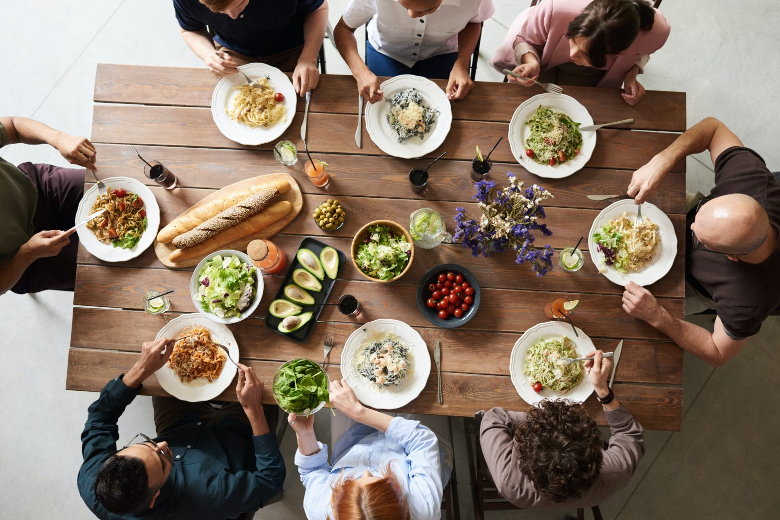 Group of colleagues seated at a table enjoying healthy meals together